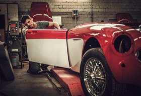 Image of man restoring car.